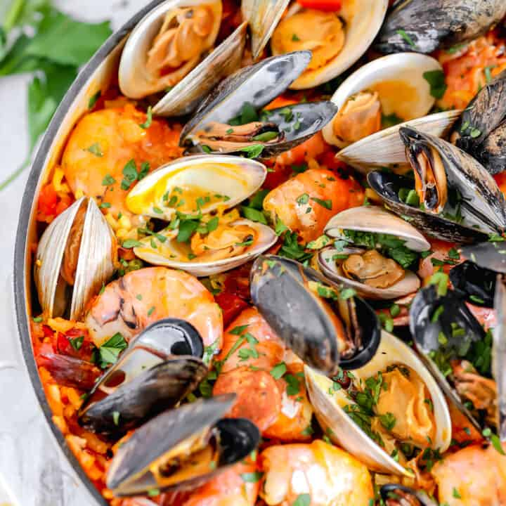 seafood paella in a cast iron with shrimp, clams, mussels on top