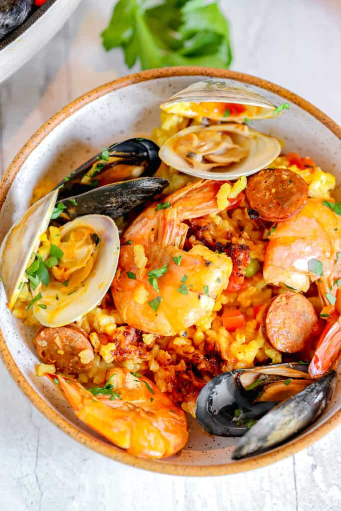 small bowl of paella with clams mussels and shrimp