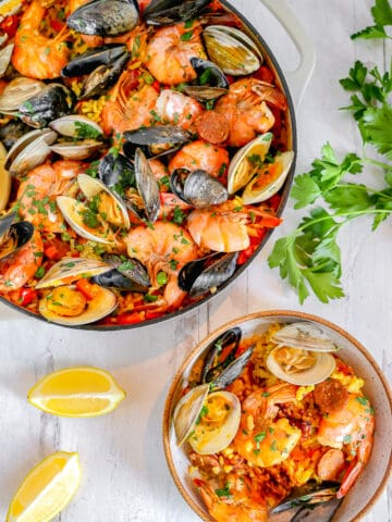 skillet of seafood paella with a smaller bowl