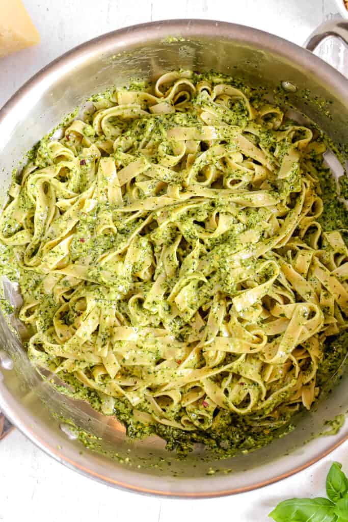 pasta noodles in pan coated in creamy pesto sauce