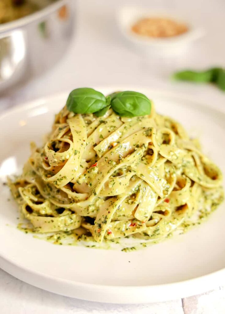 pile of pesto pasta on a white plate with a basil leaf on top