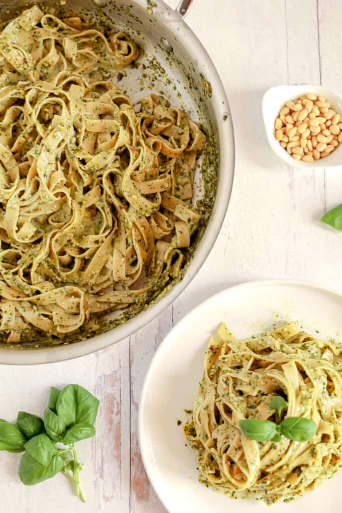 pesto pasta noodles in a skillet with a plate of pesto pasta