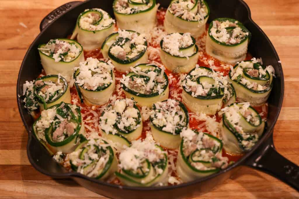 zucchini rolls topped with shredded cheese