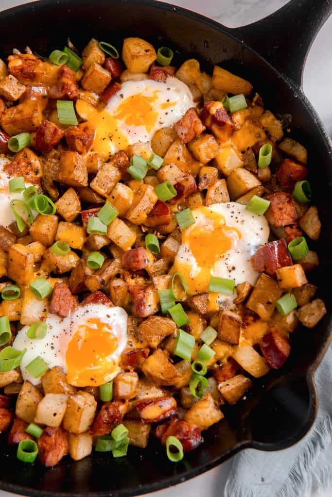 overhead shot of breakfast potatoes, chorizo, baked eggs with runny yolks, and green onions in a cast iron skillet
