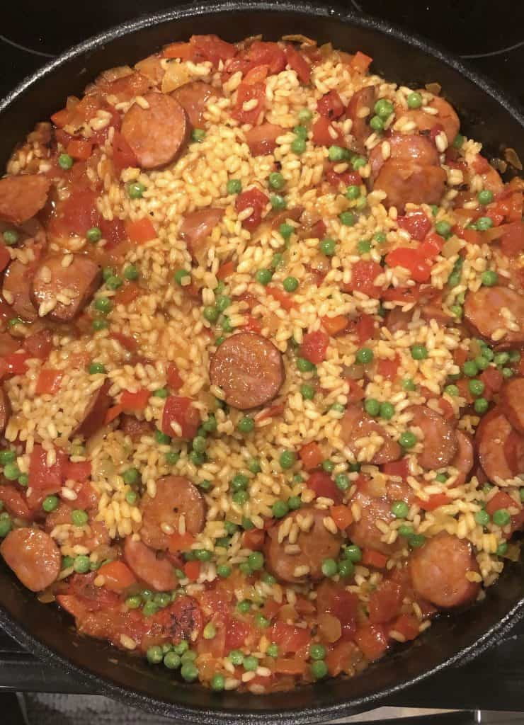 overhead photo of the paella and chorizo in a cast iron skillet