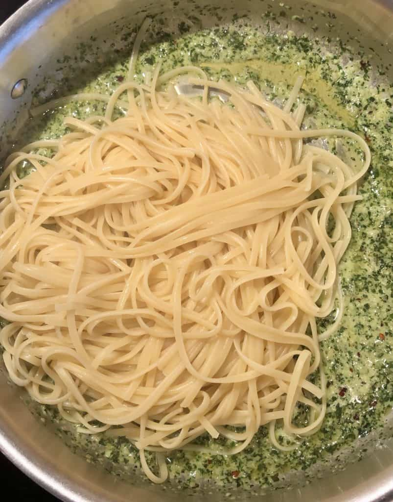 skillet with creamy pesto pasta sauce with fresh linguine added on top