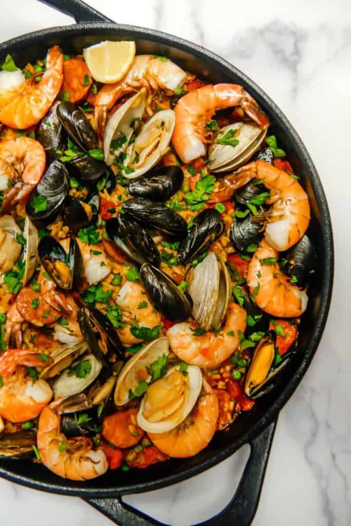 close up of seafood and chorizo paella with shrimp, mussels, clams, in a cast iron skillet