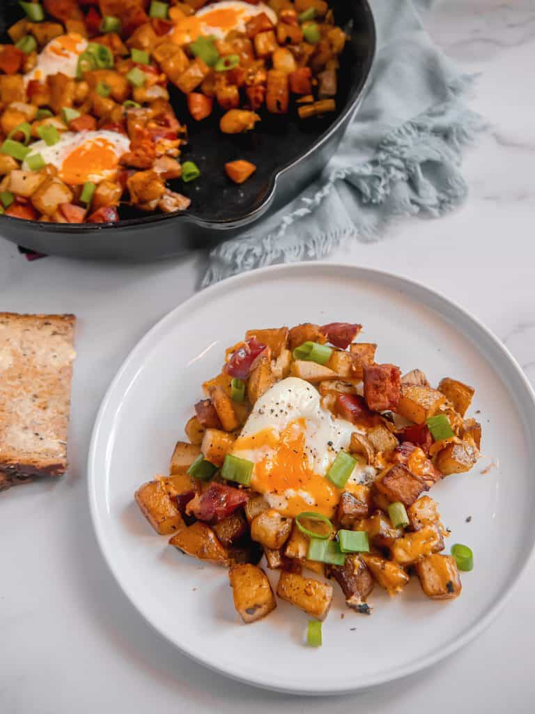 white plate with breakfast potatoes, chorizo, runny egg, with cast iron skillet in background, and buttered toast