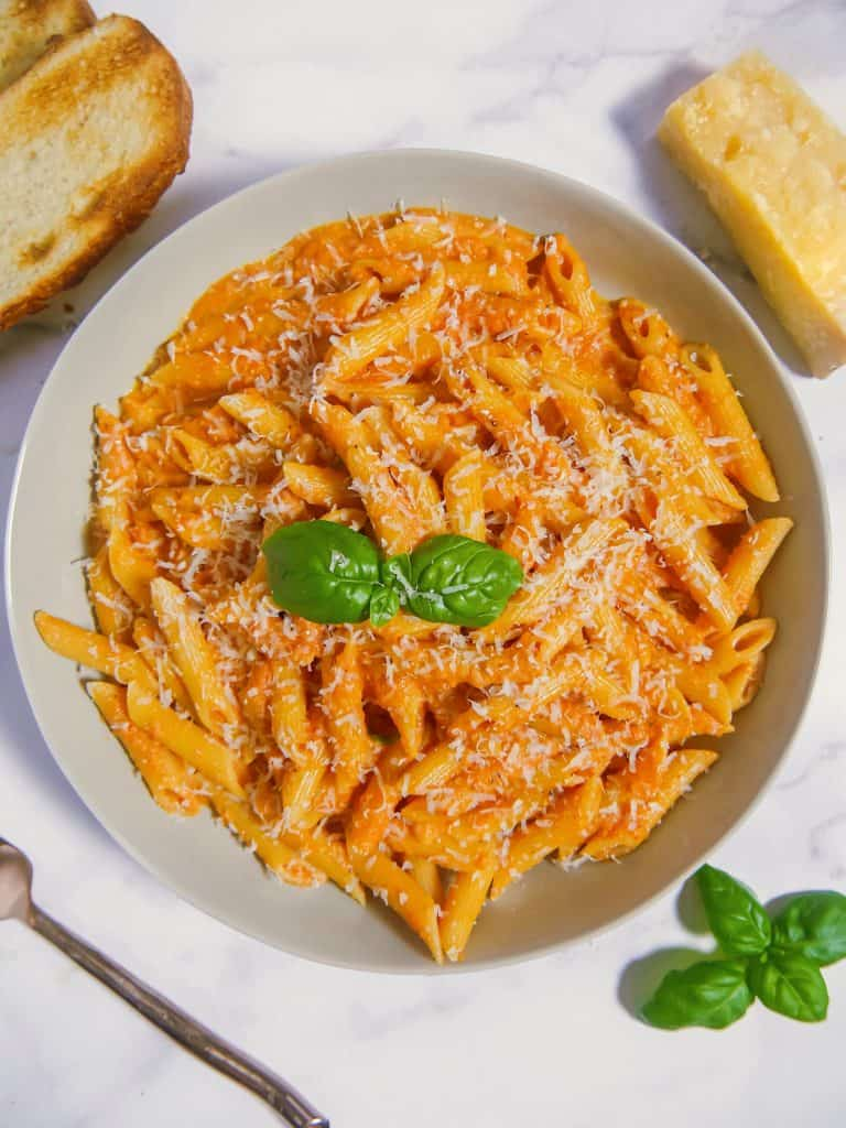 overhead shot of a grey bowl filled with penne alla vodka with fresh basil, a block of parmesan, and toast surrounding