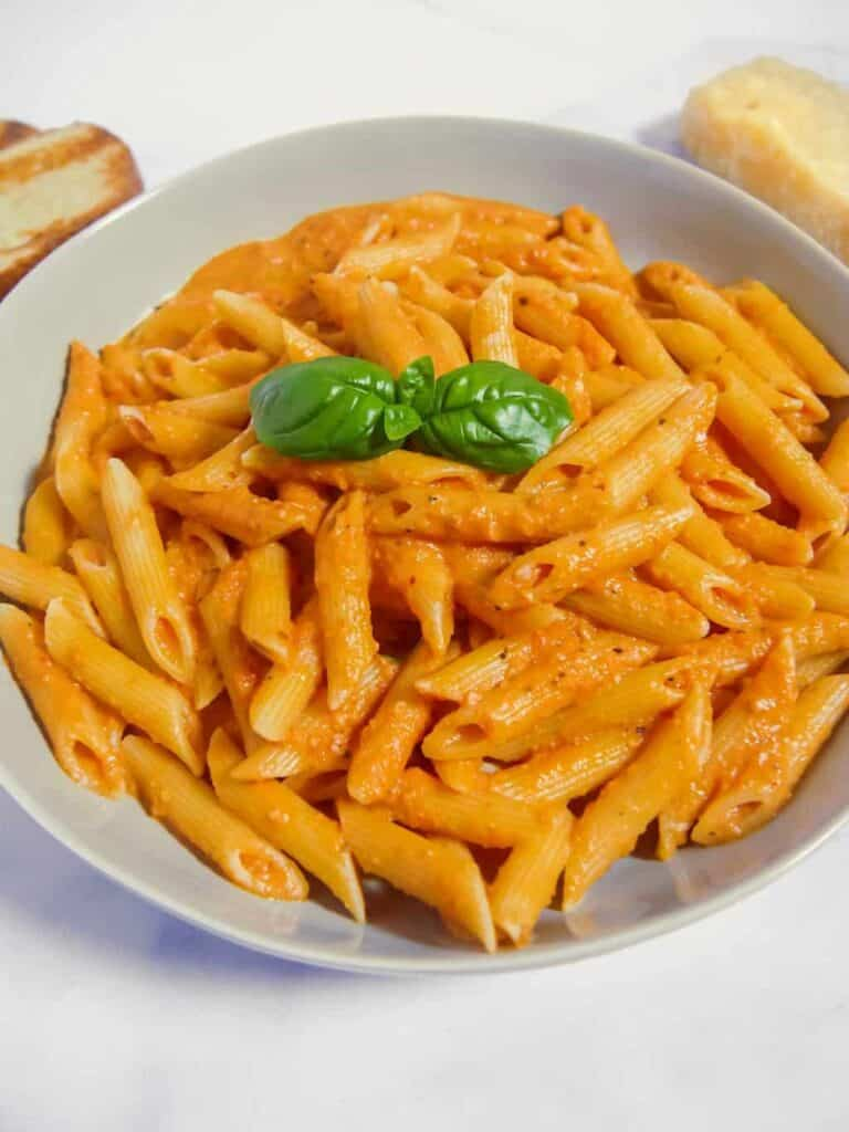 frontal shot of a grey bowl filled with penne alla vodka with fresh basil, a block of parmesan, and toast surrounding
