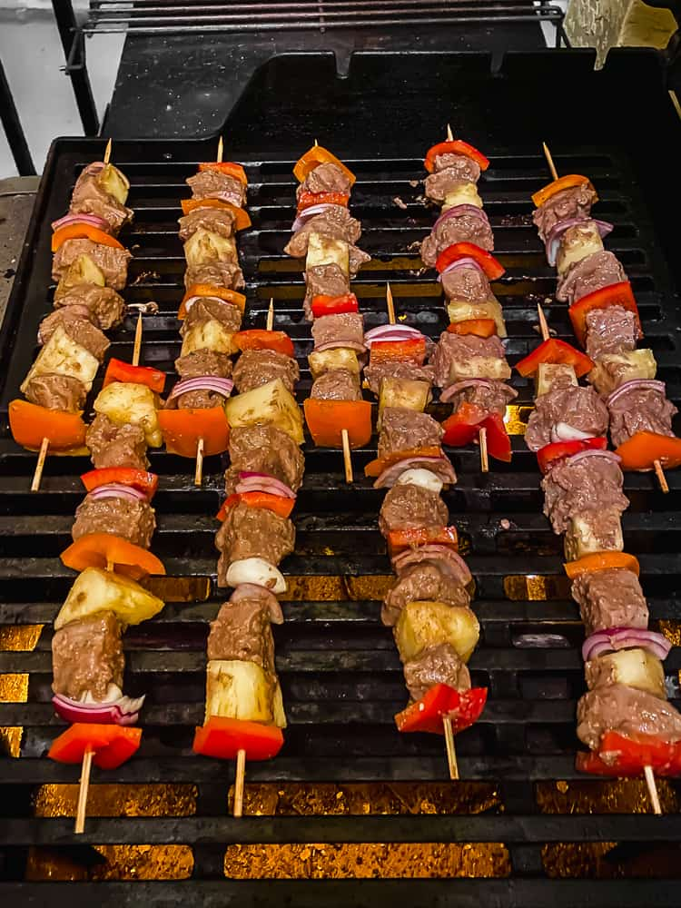jerk chicken skewers cooking on a grill