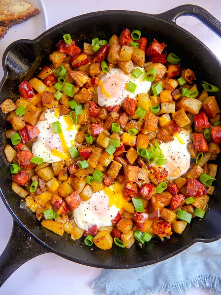 cast iron skillet with chorizo, diced potatoes, baked eggs, and cheese with green onion garnish