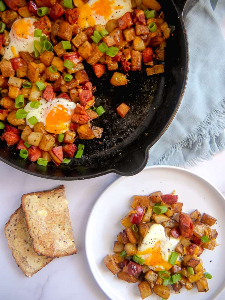 cast iron skillet with chorizo, diced potatoes, baked eggs, and cheese with green onion garnish side of toast and plate with potato dish on it