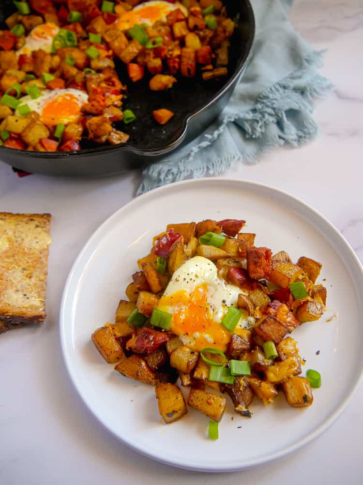 White plate with chorizo potato egg hash on it, side of buttered toast, and cast iron skillet in the background