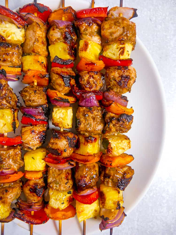 jerk chicken skewers on a white plate with grilled pineapple and peppers