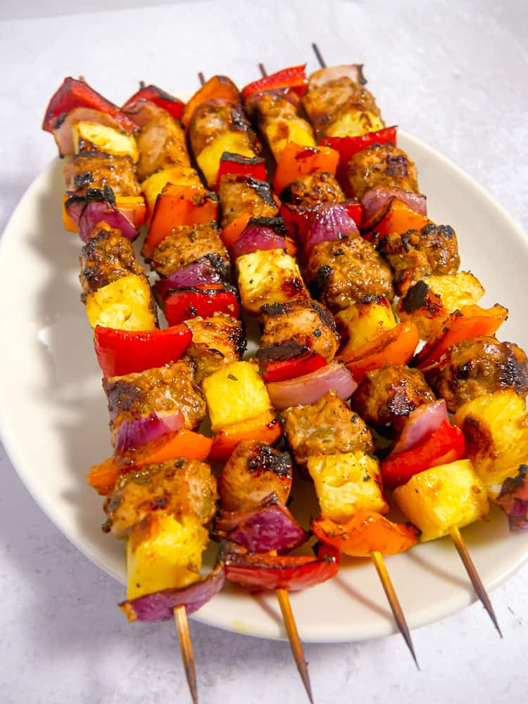skewered jerk chicken with pineapple and veggies on a whte plate