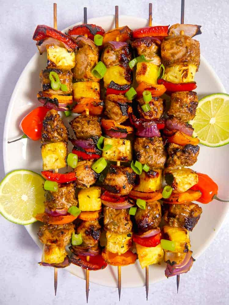skewers with jerk chicken. pineapple, onion, and bell peppers on a white plate