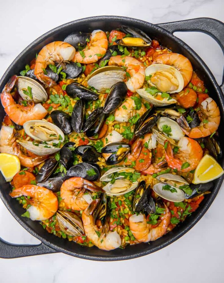 seafood and chorizo in a cast iron skillet with rice peas and herbs