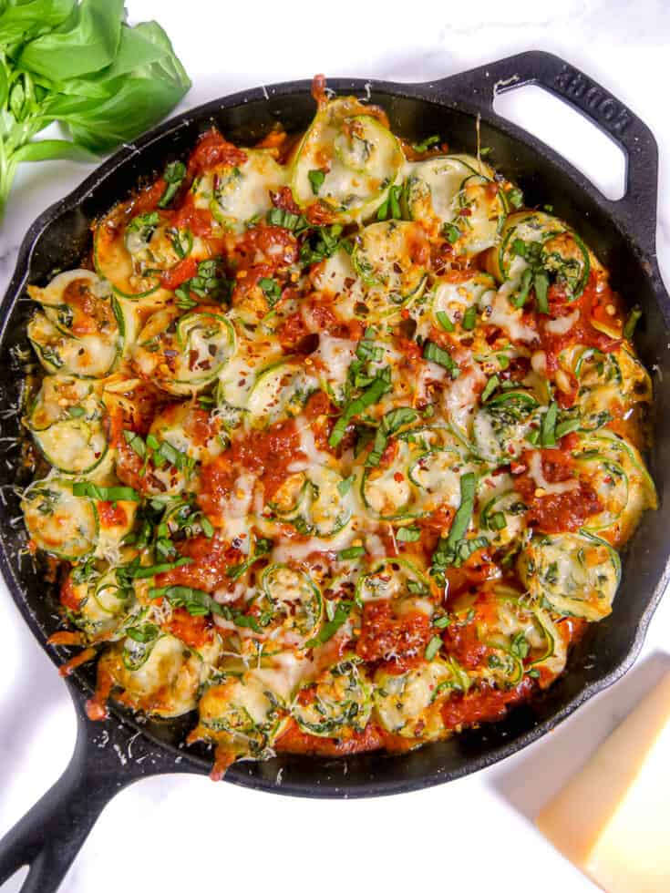 close up of cast iron skillet stuffed with zucchini rolls and red sauce