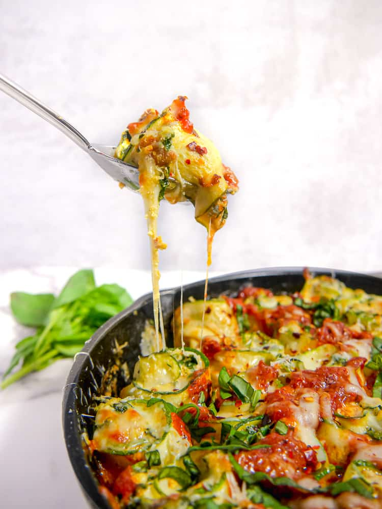 a cheesy zucchini roll being lifted out of a cast iron skillet with a fork