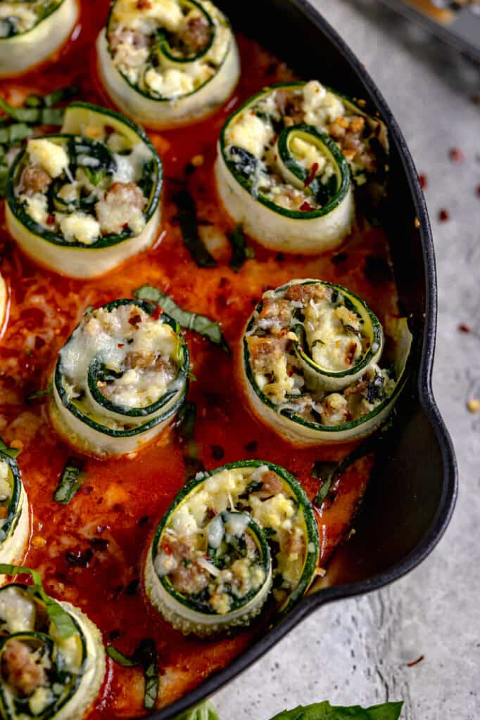 close up of stuffed zucchini rolls in red sauce in cast iron
