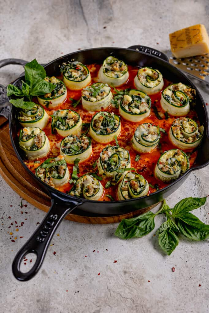 skillet with stuffed zucchini rolls, fresh basil leaves, and block of parmesan