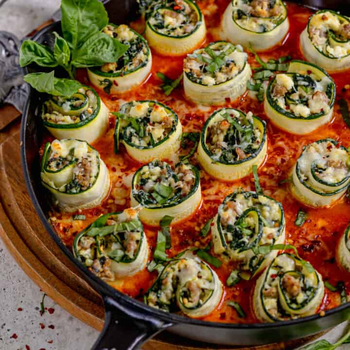 stuffed zucchini rolls in a cast iron skillet with red sauce