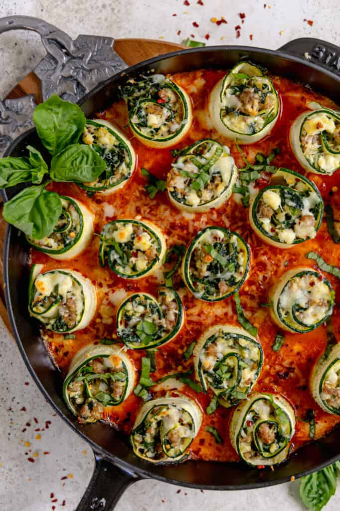 zucchini involtini in a bed of red sauce in a cast iron skillet topped with fresh basil