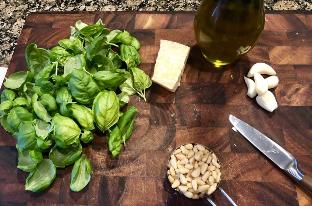 overhead shot of basil leaves, parmesan cheese block, pine nuts, garlic cloves, and olive oil on a wooden cutting board