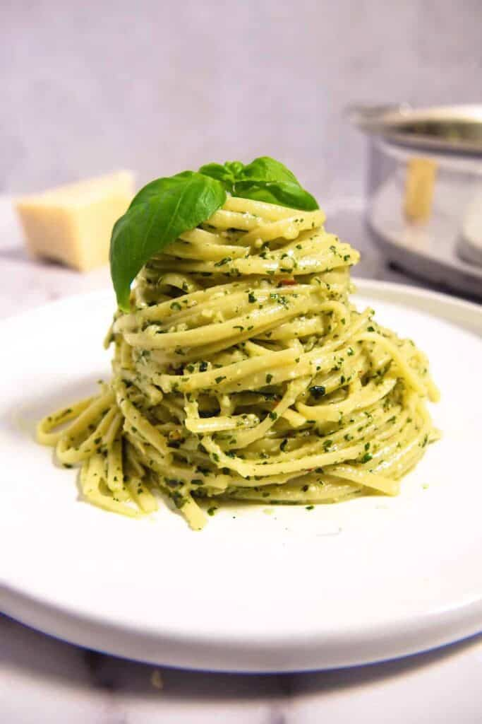 front photo of a mound of linguini in the creamy pesto pasta sauce on a white plate with Fresh basil leaves on top