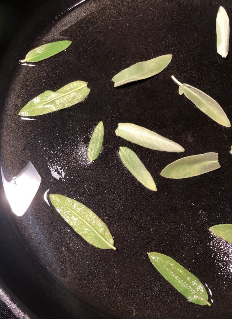 fresh sage leaves in a cast iron skillet with olive oil