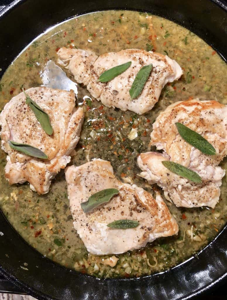 cast iron skillet with white wine sauce, four chicken breast topped with sage leaves