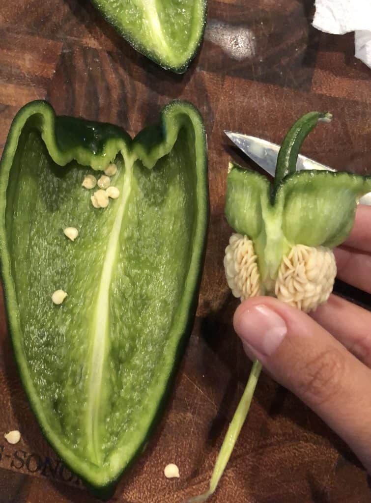 cut stem out of a poblano pepper with half on cutting board
