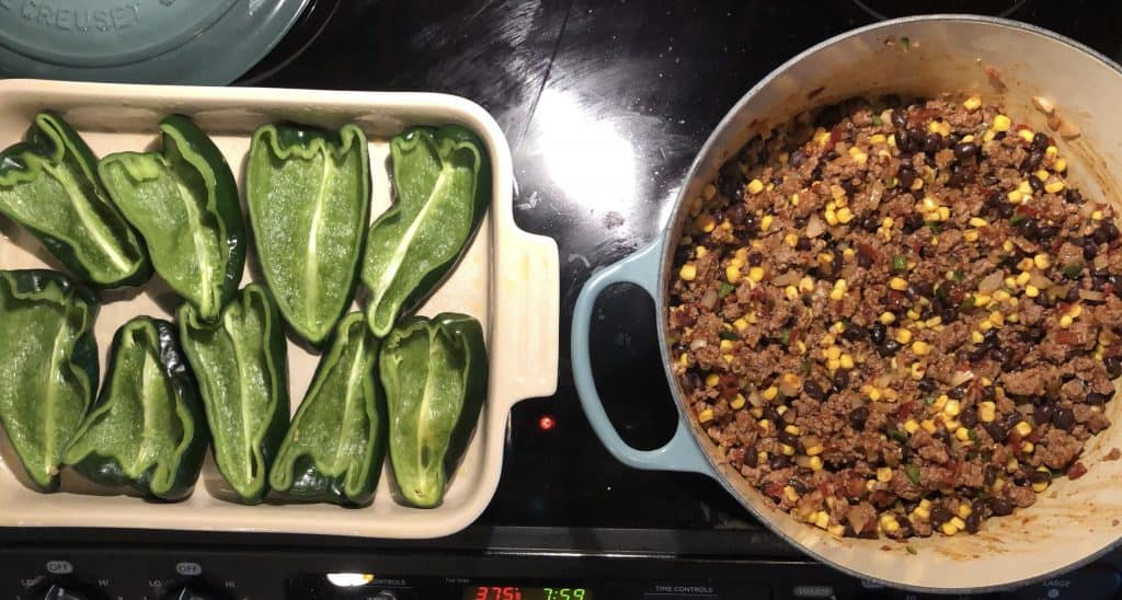 over head shot of ground beef mixture in dutch oven and poblano peppers in a baking dish