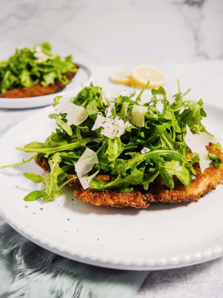front  shot of  chicken milanese on a white plate with arugula piled on top and shaved parmesan with a second one in the background