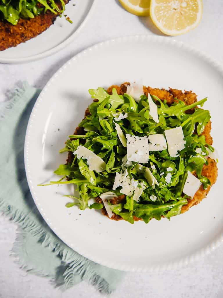 overhead shot of  chicken milanese on a white plate with arugula piled on top and shaved parmesan
