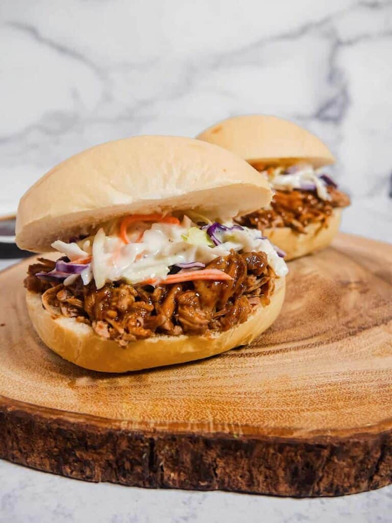 Front shot picture of two bread buns with shredded pork covered in BBQ sauce, with coleslaw on top, on top of a wooden board