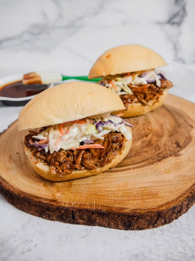 Front shot picture of two bread buns with shredded pork covered in BBQ sauce, with coleslaw on top, on top of a wooden board with bbq sauce in the background