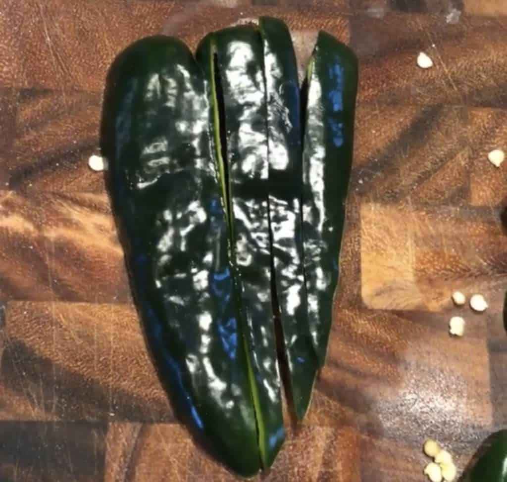 poblano pepper with vertical cuts on a cutting board