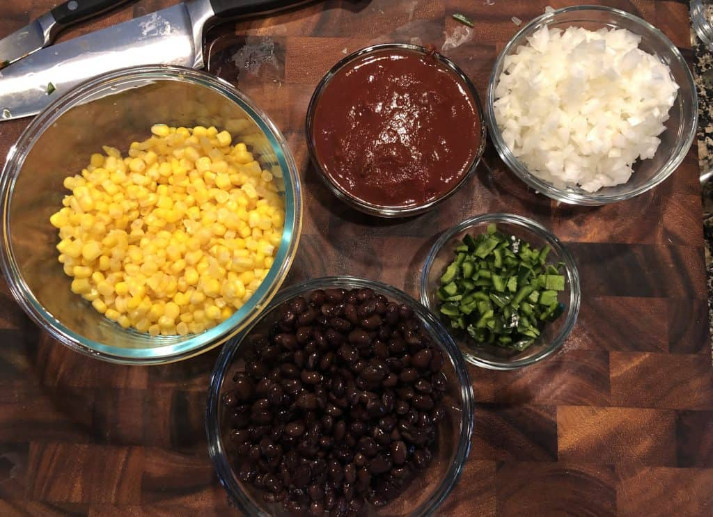 overhead shot of a bowl of corn, black beans, poblano peppers, chipotles in adobo, and diced onion