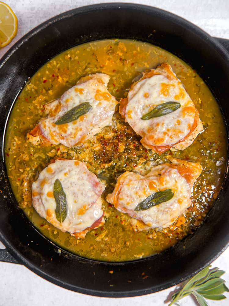 cast iron skillet with four pieces of chicken covered in cheese, prosciutto, and a sage leaf