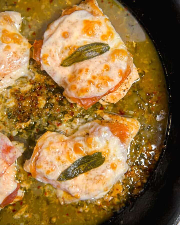 cast iron skillet with 3 pieces of chicken covered in cheese, prosciutto, and a sage leaf