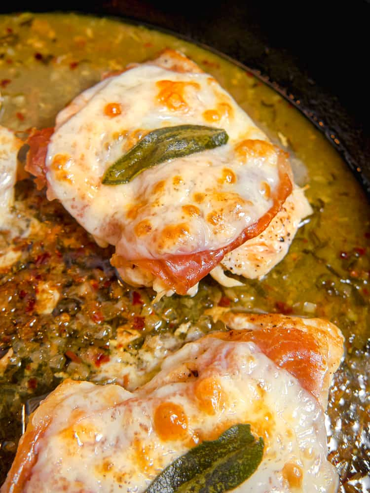 close up of chicken saltimbocca in a cast iron skillet, chicken breast with sage and brown bubbly cheese on top