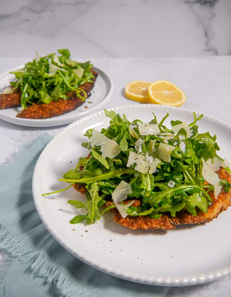two breaded chicken milanese with arugula salad and fresh parm grated on top
