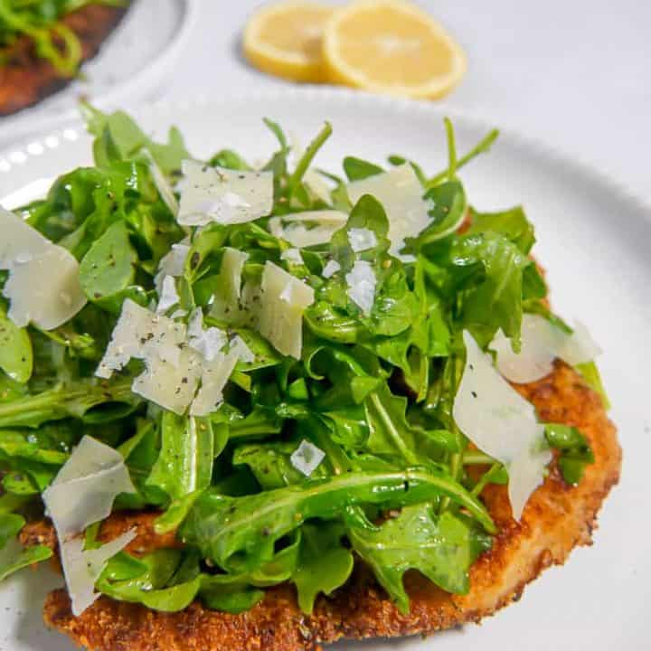close up photo of chicken cutlet with arugula salad on top on a white plate