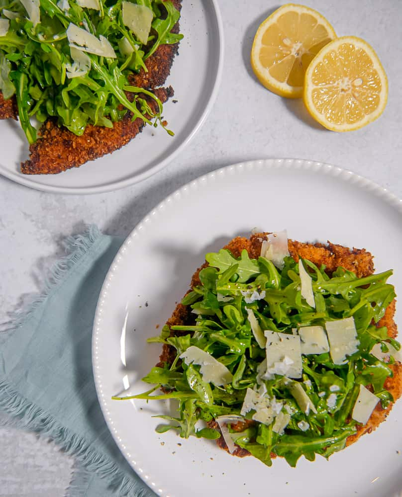 overhead photo of two breaded chicken cutlets topped with arugula salad on plates