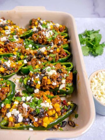 baking dish with poblano peppers stuffed with beef, black beans, corn