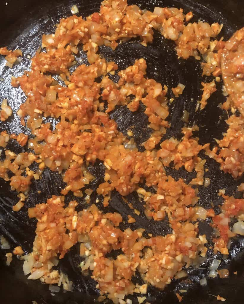 sautéd onion, garlic, and ginger in red curry paste in a cast iron skillet