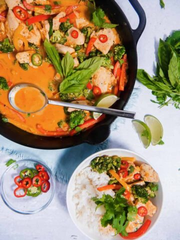 overhead shot of a cast iron skillet with curry chicken topped with basil and jalapeños, with a bowl of rice with curry poured over the top, and bowl of hot peppers