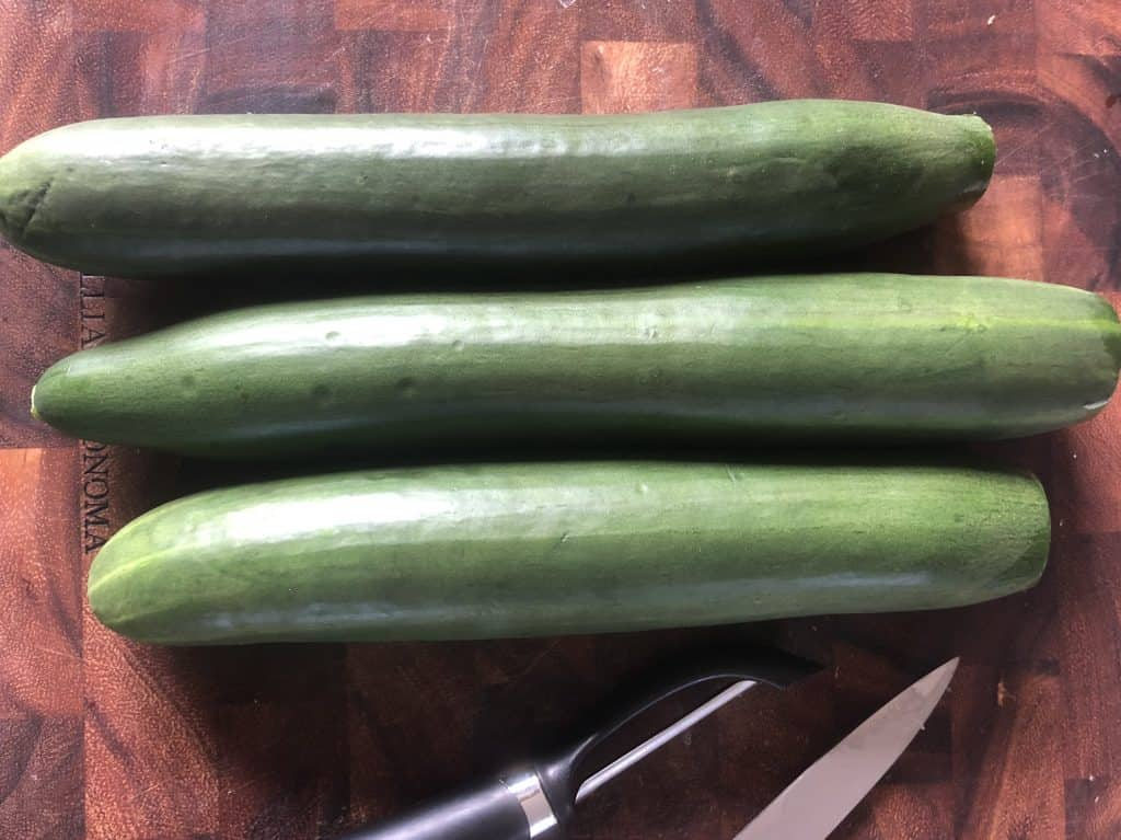 three whole cucumbers on a cutting board